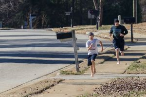 Man and boy running on residential sidewalk